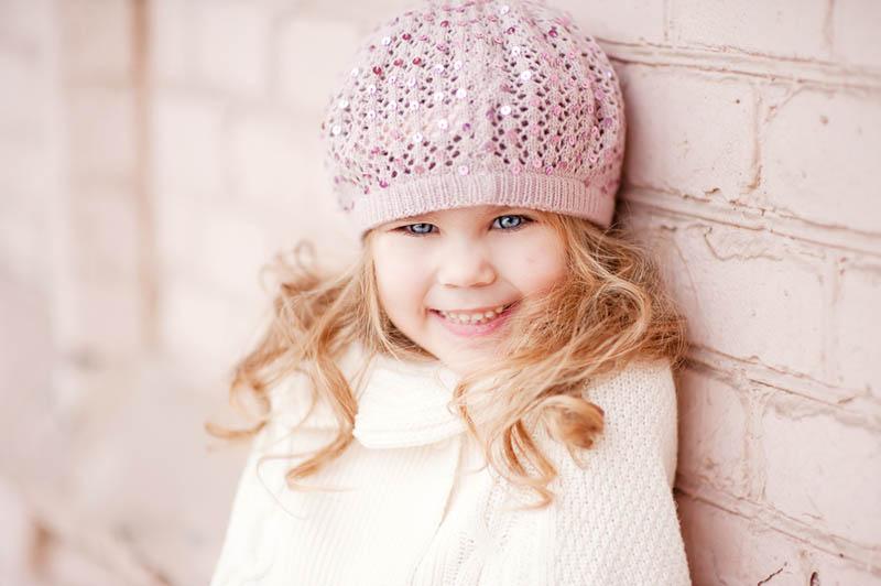 schönes Mädchen mit blonden Augen trägt einen Hut an der Wand stehen im Freien