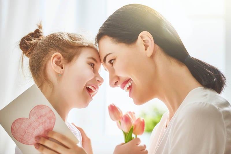 süßes kleines Mädchen kuscheln mit Mutter für ihren Geburtstag
