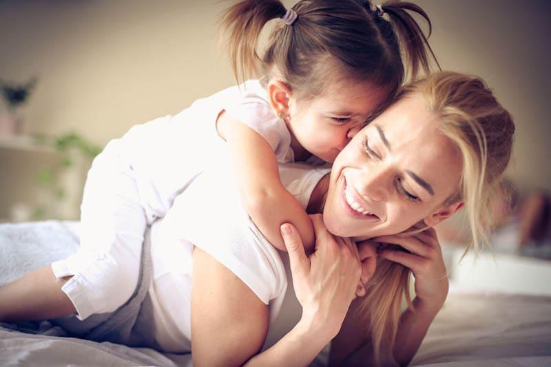 süßes kleines Mädchen küsst ihre Mutter