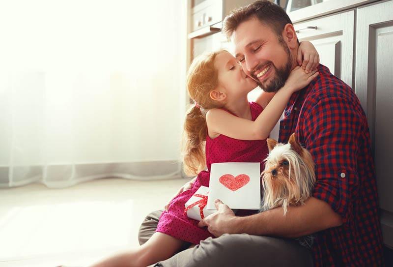 süßes kleines Mädchen küsst ihren Vater mit Hund in seinen Händen