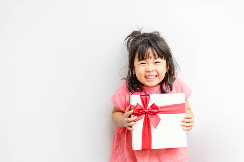 süßes kleines Mädchen lächelnd, während ein Geschenk halten