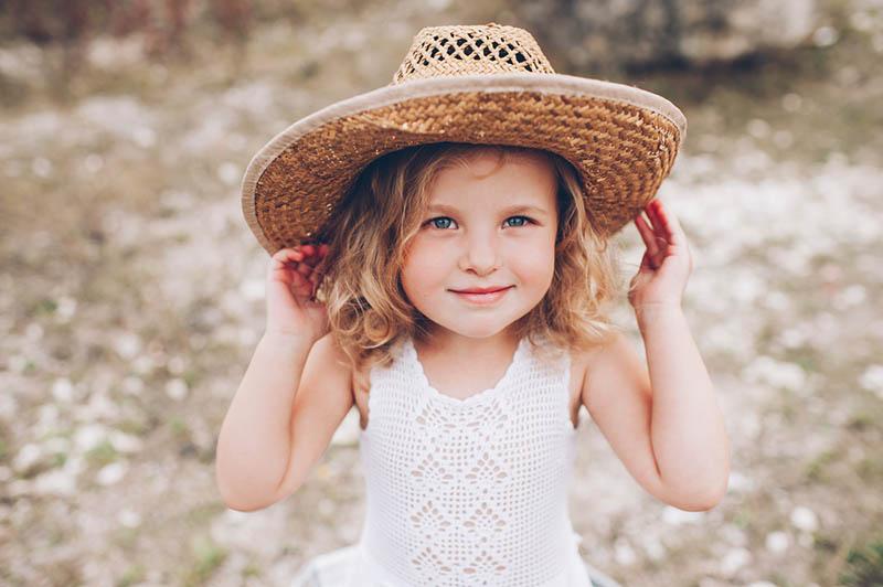 süßes kleines Mädchen posiert mit Hut im Freien