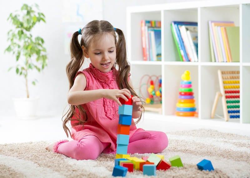 süßes kleines Mädchen spielt mit Spielzeug auf dem Boden