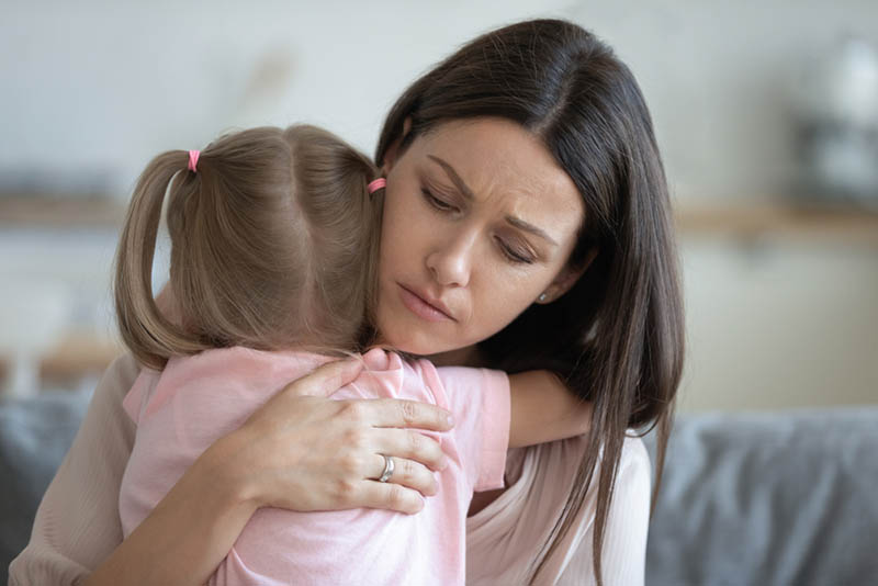 traurige Mutter umarmt mit kleiner Tochter auf der Couch