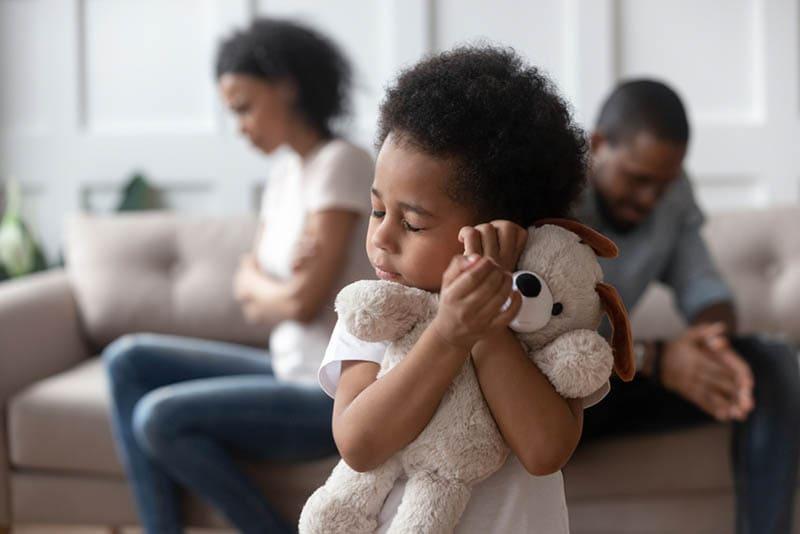 trauriger kleiner Junge umarmt Spielzeug, während Eltern im Konflikt