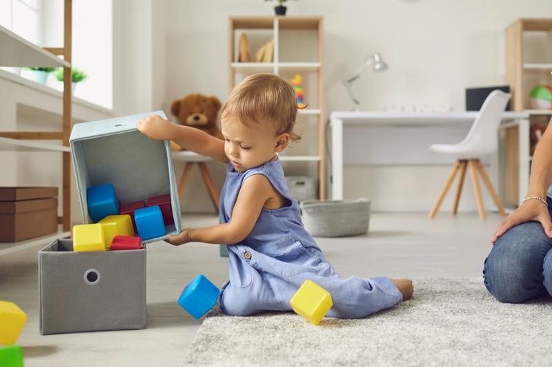 2-jähriges Kind, das nach dem Spielen Würfel zurück an ihren Platz legt