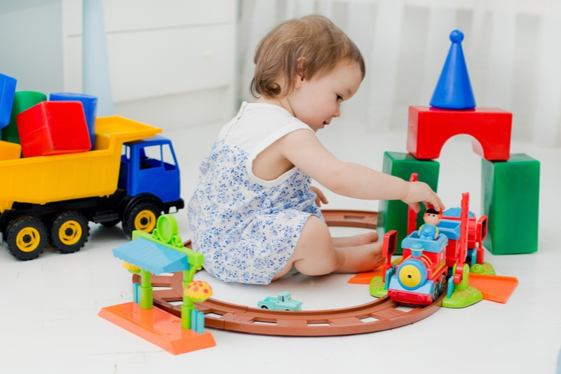 Baby 2 Jahre alt spielt mit vielen bunten Plastikspielzeugen im Haus