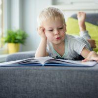 Dreijähriger Junge liegt auf dem Bauch auf dem Sofa und liest ein Kinderbuch