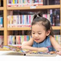 kleines Mädchen liest ein Kinderbuch in der Bibliothek