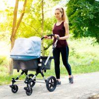 Mutter trainiert beim Gehen mit Kinderwagen