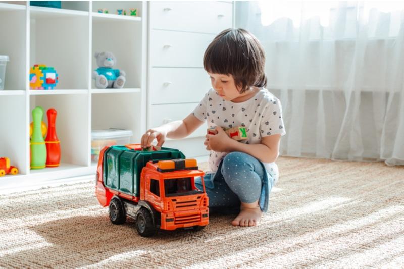 Dreijähriges Mädchen, das zu Hause mit einem Spielzeugauto spielt