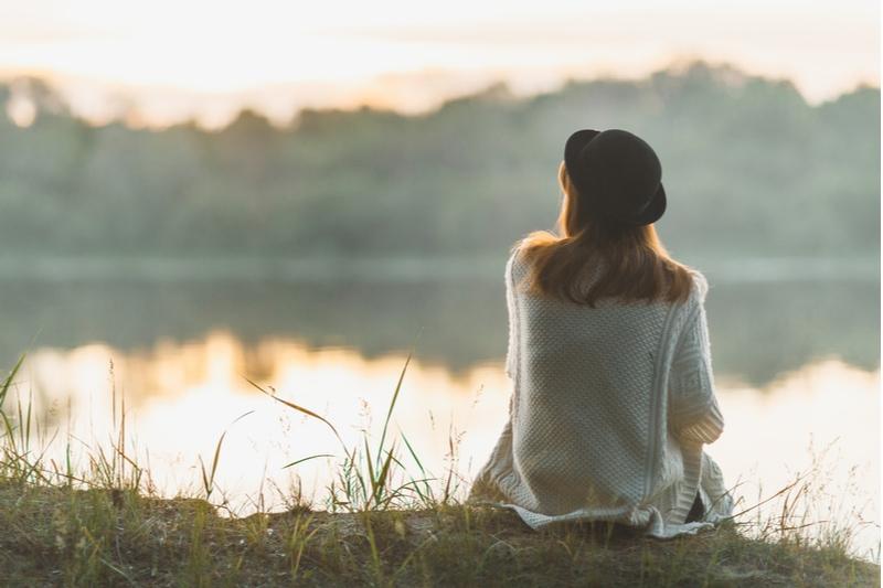 Ein Mädchen sitzt schweigend am Flussufer