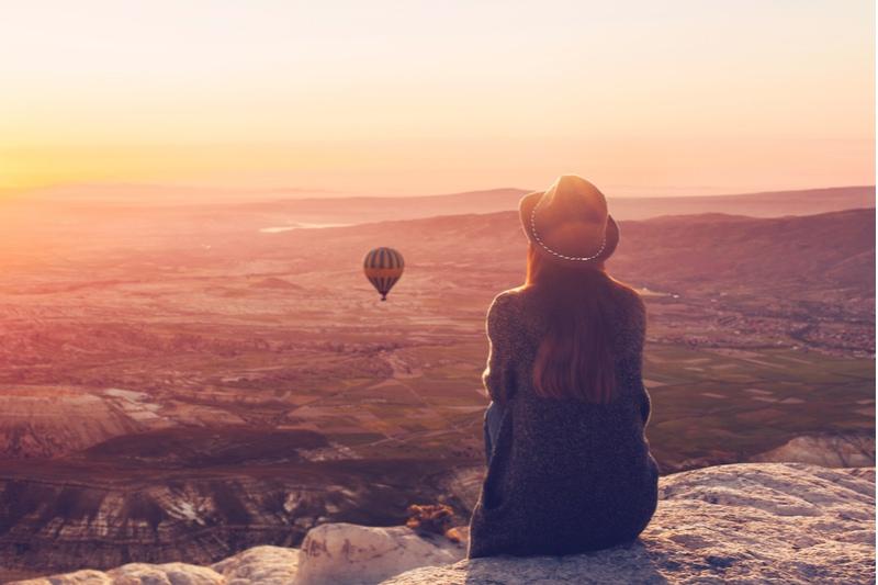 Eine Frau allein auf einem Hügel bewundert die ruhige Naturlandschaft