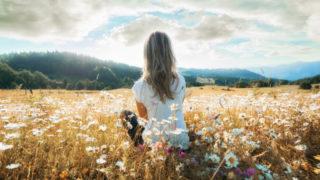 Frau mit blondem Haar sitzt in einem Blumenfeld