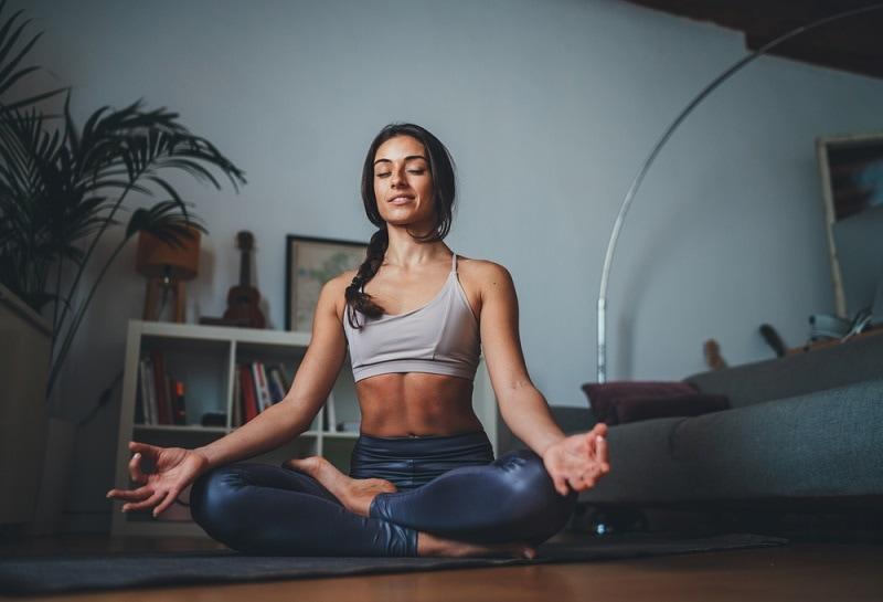 junge Frau meditiert in ihrem Wohnzimmer