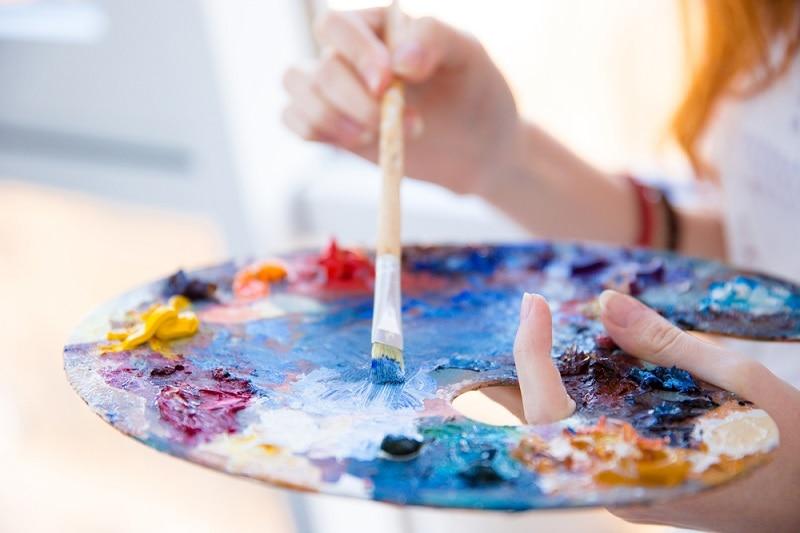 Junge Frau mischt Farbe mit einem Pinsel