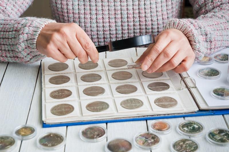 Frau ordnet Münzen auf dem Tisch