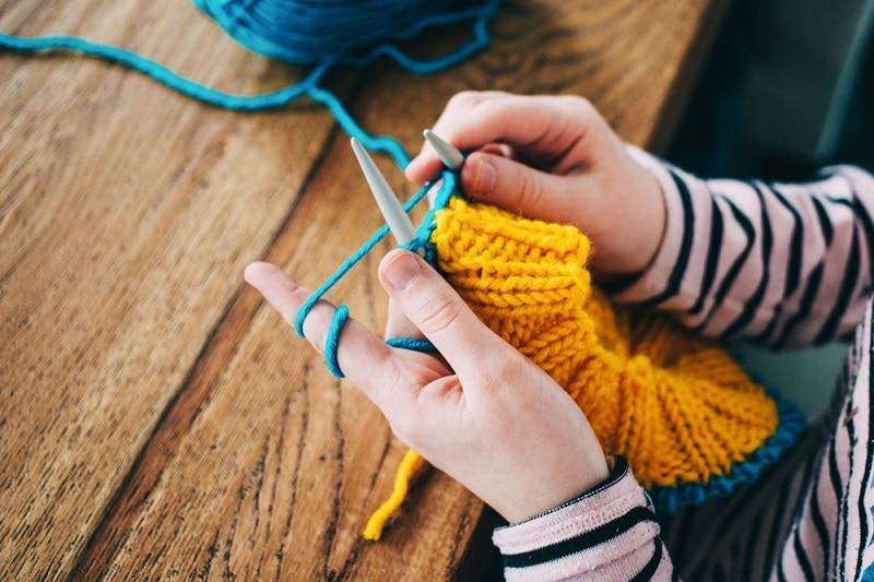 Frau strickt einen gelben Schal
