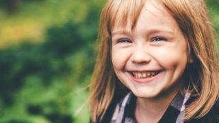 glückliches kleines Mädchen lacht beim Stehen in der Natur