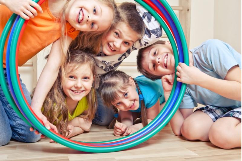 Fünf fröhliche Kinder, die durch Hula-Hoop-Reifen schauen