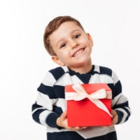 5 Jahre alter Junge hält eine rote Geschenkbox