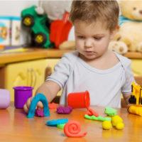 Zweijähriges Kind spielt mit Spielzeug im Kinderzimmer