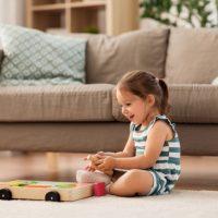glückliches 3-jähriges Mädchen, das mit einem Holzspielzeug auf dem Boden spielt