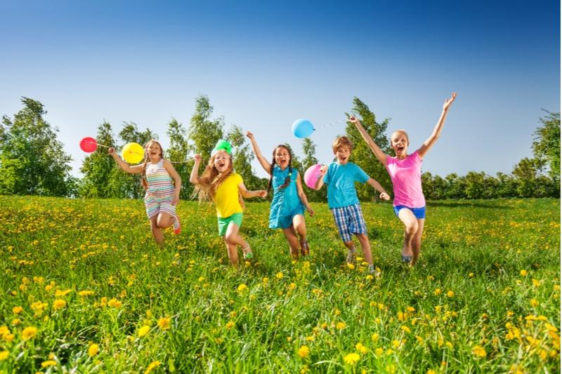 Glückliche fünf Kinder mit Ballons laufen im Feld