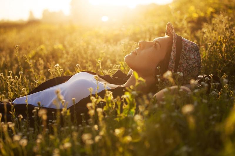 Glückliches Mädchen liegt an einem Sommerabend zwischen den Wildblumenflower
