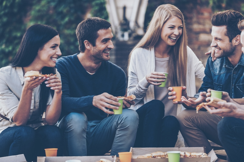 Gruppe fröhlicher junger Leute, die miteinander reden und Pizza essen
