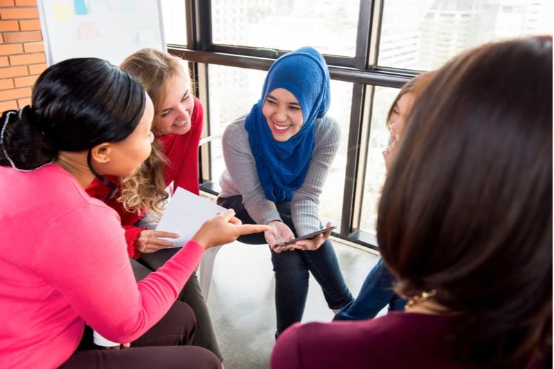 Gruppe von Freunden, die im Kreis sitzen und lächeln