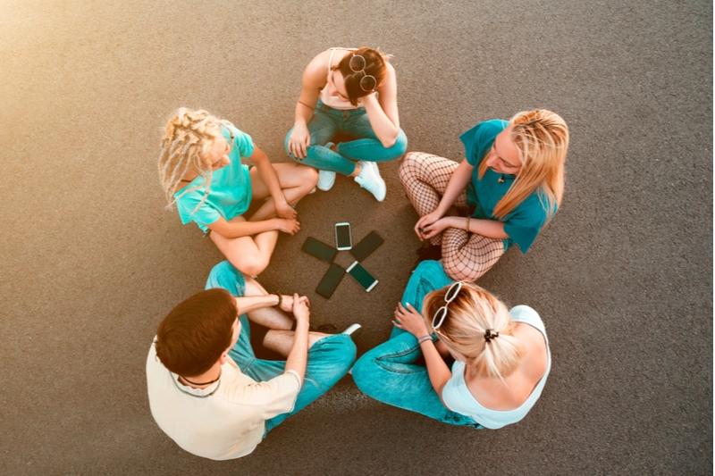 Junge Leute sitzen auf dem Boden mit Handys im Kreis