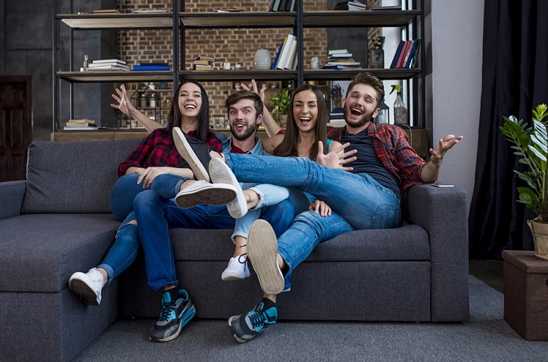 glückliche junge Leute, die auf der Couch ein Spiel spielen