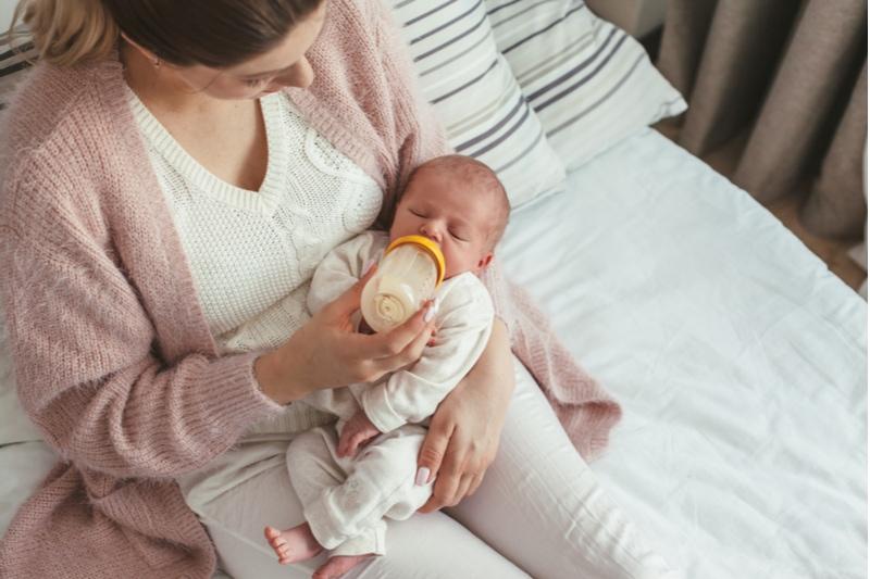 Junge Mutter füttert ihr Kind aus der Flasche