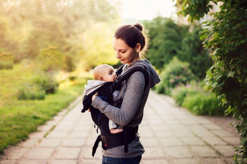Junge Mutter tragt Baby in einer Tragehilfe drausen im Park