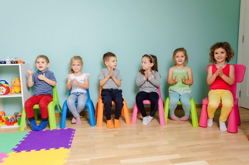 Kinder spielen ein Spiel, während sie auf bunten Stühlen sitzen