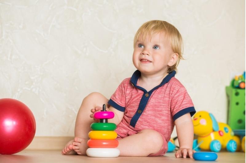 Kleinkind sitzt auf dem Boden und spielt mit einem bunten Spielzeug