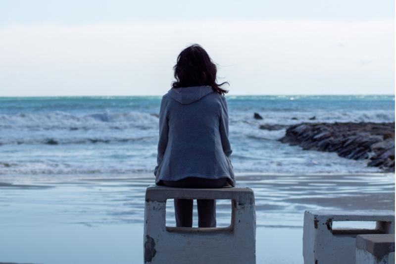 Mädchen allein mit Blick auf das Meer