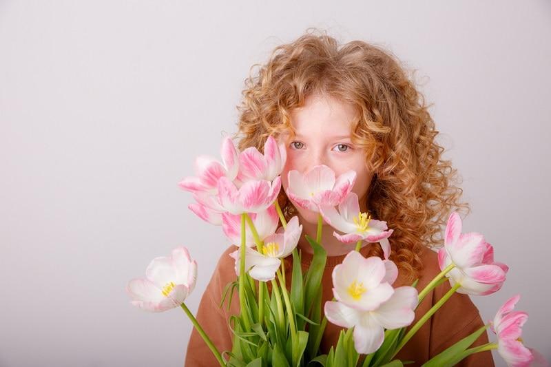 Mädchen mit lockigen Haaren hält sich rosa Blumen vor das Gesicht