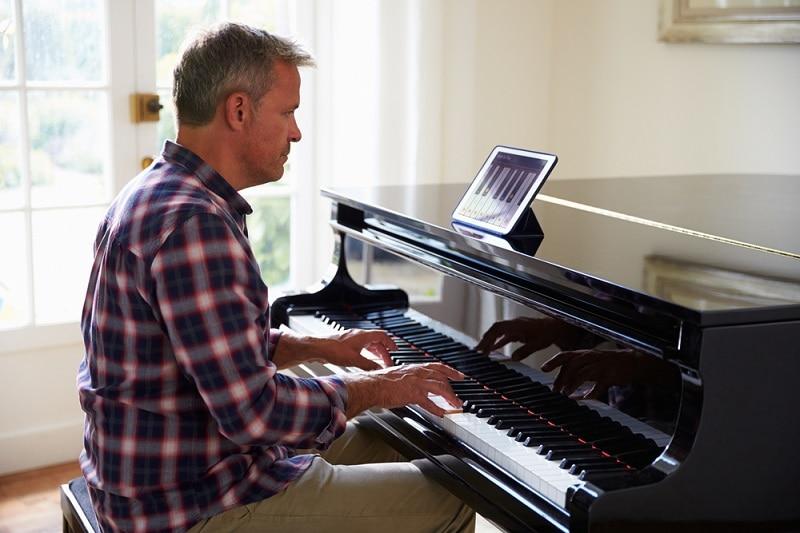 Mann lernt zu Hause das Klavierspielen