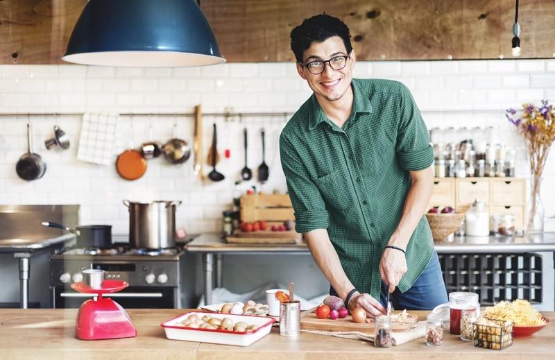 gut aussehender junger Mann mit Brille kocht in der Küche