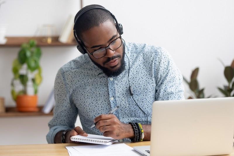 ein junger Mann mit Brille lernt eine neue Sprache auf seinem Laptop