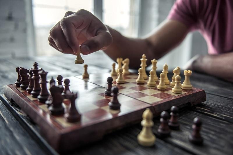 junger Mann spielt Schach zu Hause