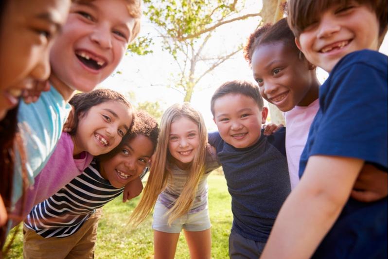 Multiethnische Gruppe von Schulkindern, die lachen und sich umarmen
