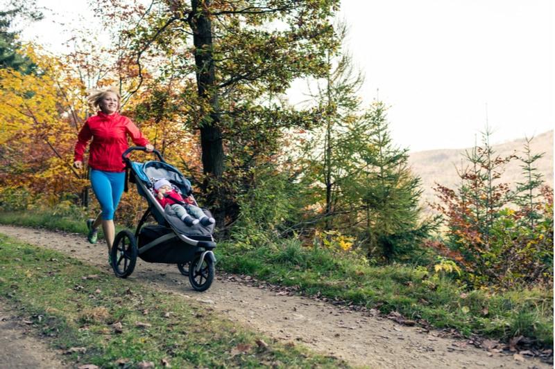 Mutter läuft mit Kind im Kinderwagen