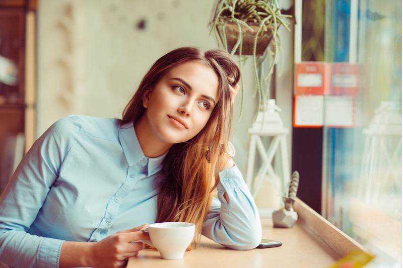 Nachdenkliche glückliche Frau in der Kaffeepause