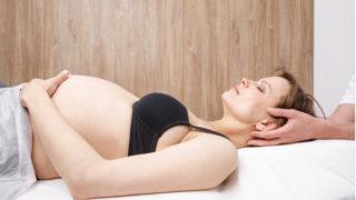eine schwangere Frau auf einem Untersuchungstisch liegend während einer osteopathischen Behandlung