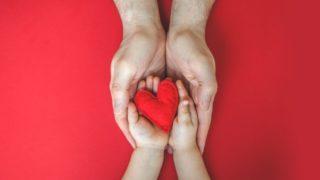Vater hält sein Kind an den Händen