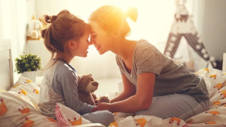 Mutter weckt morgens ihre Tochter im Bett