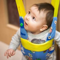 kleines Baby sitzt in einem Türhopser und schaut nach oben